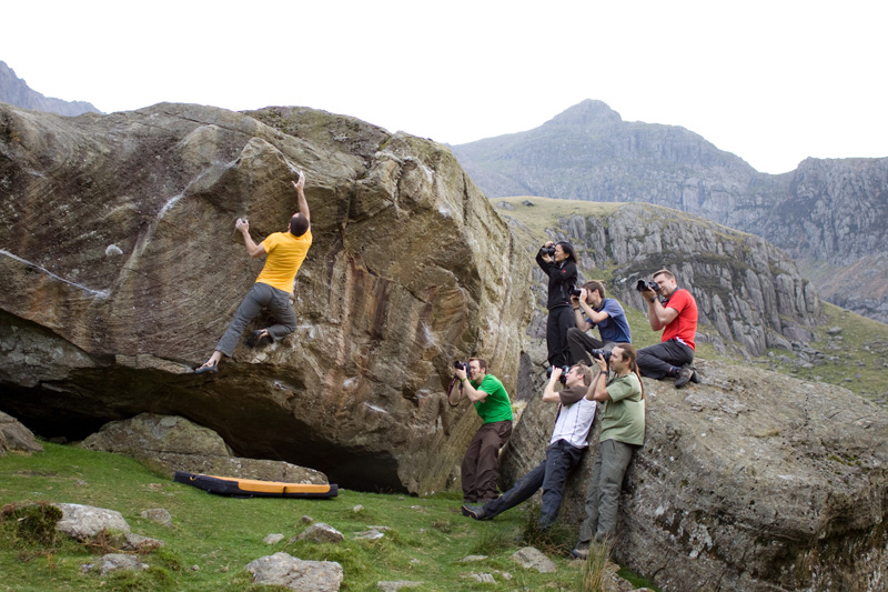 Climber on rock face being photographed by students on a workshop