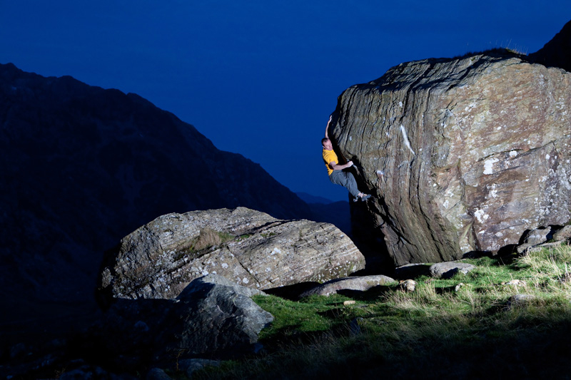 Night time shot of climbing going up rock face